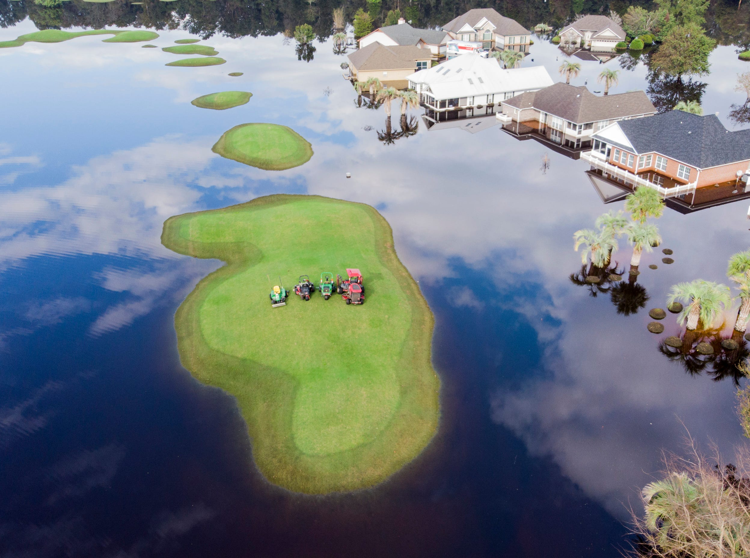 Equipment sits on a high spot on the fairway at Aberdeen Golf Course in Longs, S.C., Monday, Sept. 24, 2018. Floodwaters from the Waccamaw River are beginning to recede in the northern part of Horry County, while Conway is expected to crest on Wednesday.