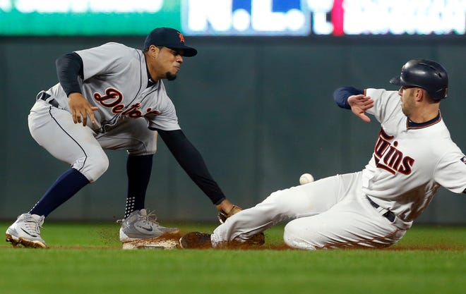 The Minnesota Twins' Joe Mauer, right, advances safely to second on a wild pitch as the throw gets past Detroit Tigers shortstop Harold Castro during the eighth inning.