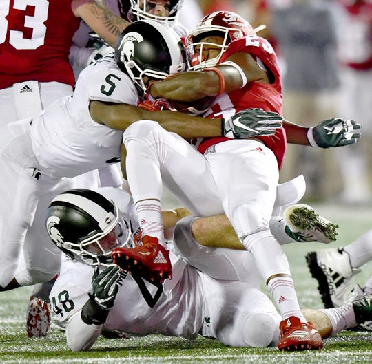Michigan State's Andrew Dowell (5) and Kenny Willekes (48) team up to stop Indiana running back Ronnie Walker short of the first-down marker last Saturday in Bloomington, Ind.