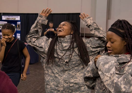 Wilnise Charles, 13, center, and Danielle Harris, 13, both Glenwood Academy students, compete in a competition at the U.S. Army booth at the JA JobSpark event at the Old National Events Plaza Wednesday afternoon. More than 3,500 students are expected to visit the two-day event to learn about careers in the Tri-State.