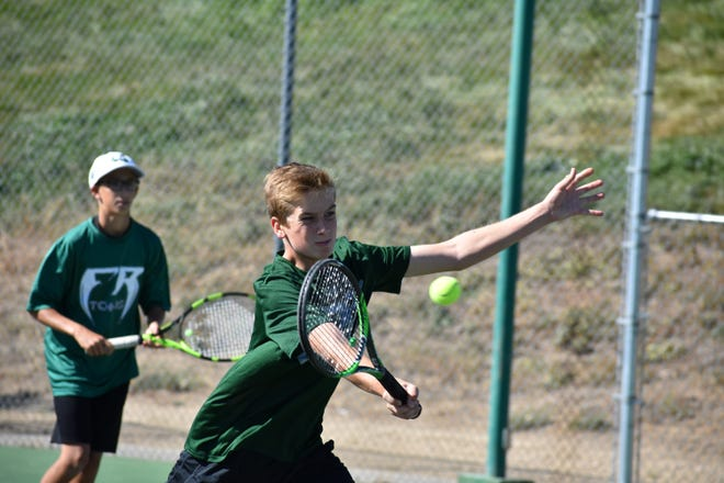 Fossil Ridge No. 4 doubles player John Shelby returns a shot while teammate Brady Elliot looks on during Thursday's Front Range League finals match against Fairview at Loveland High School