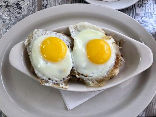 River District Cafe's breakfast boat starts with a base of fresh biscuits layered with bacon, sunny-side up eggs, and a choice of Hollandaise or sausage gravy.