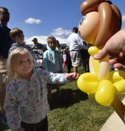 Aria Scherer of Two Rivers reaches for a balloon doll created by Mark Paul on Sept. 8 at Corn Fest in Carlsville.