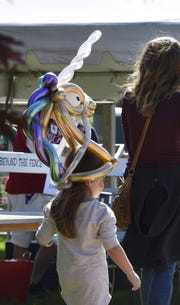 Cora Balke of Appleton wears a unicorn hat created from chrome-colored balloons by Mark Paul on Sept. 8 during Corn Fest in Carlsville.