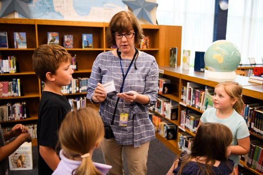Lisa Aucoin hands out library slips to third grade students after reading to them at the Summit Drive Elementary School library on Monday, Sept. 24, 2018.