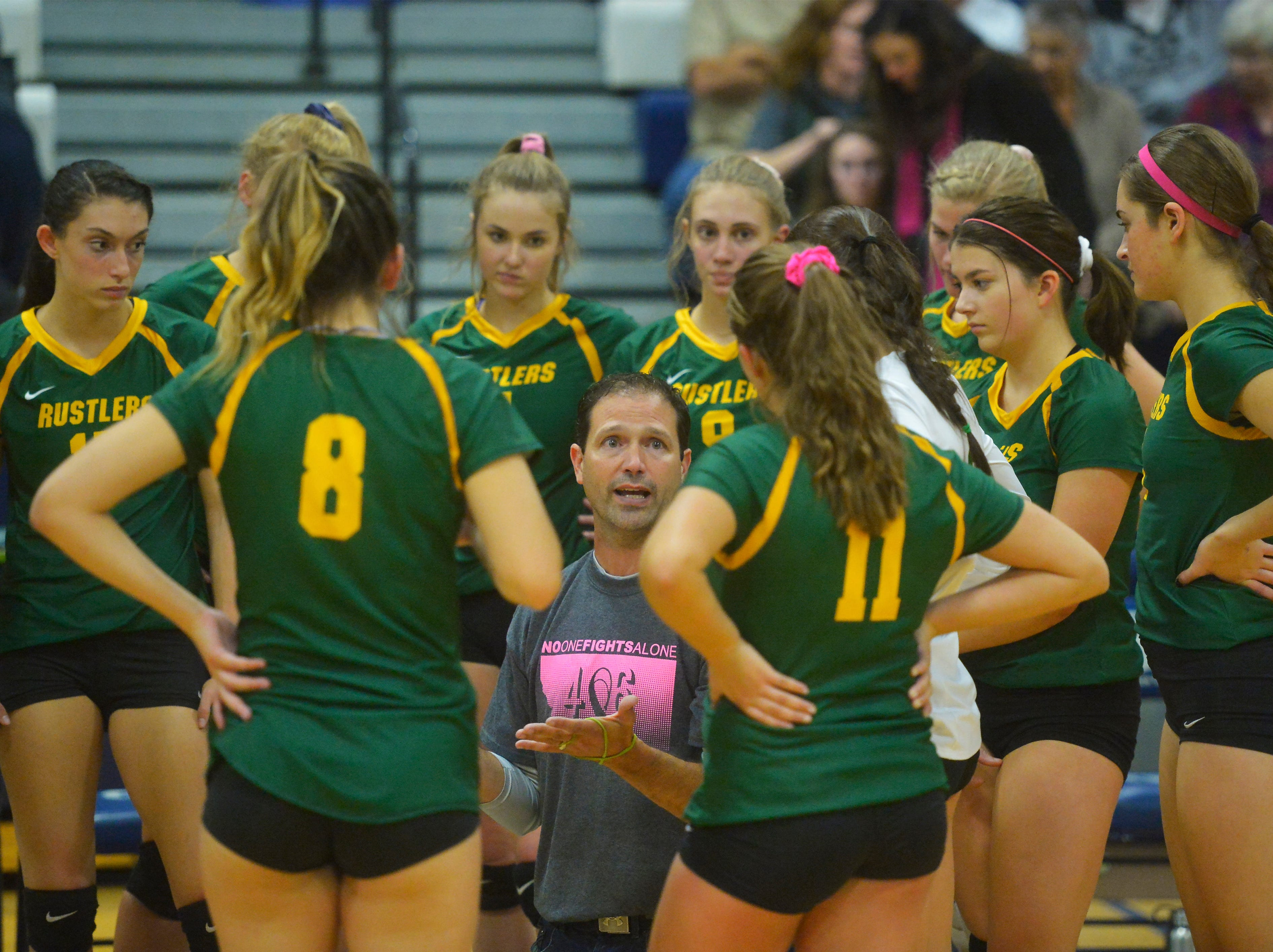 CMR coach Patrick Hiller huddles with his team during the crosstown volleyball match in the Swarthout Fieldhouse, Tuesday.