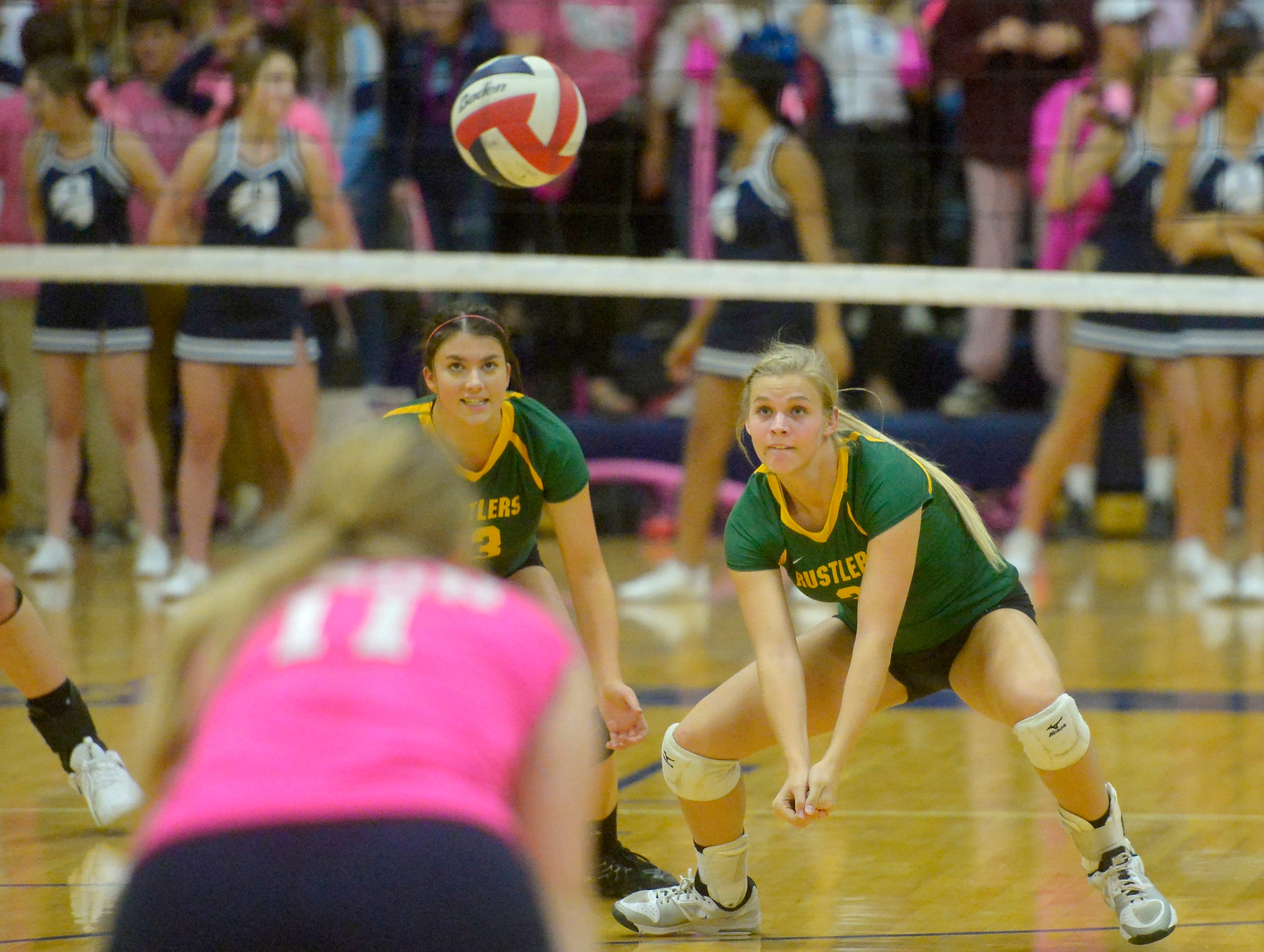 CMR's Ally Dube, left, and Teagan Taylor during the crosstown volleyball match in the Swarthout Fieldhouse, Tuesday.