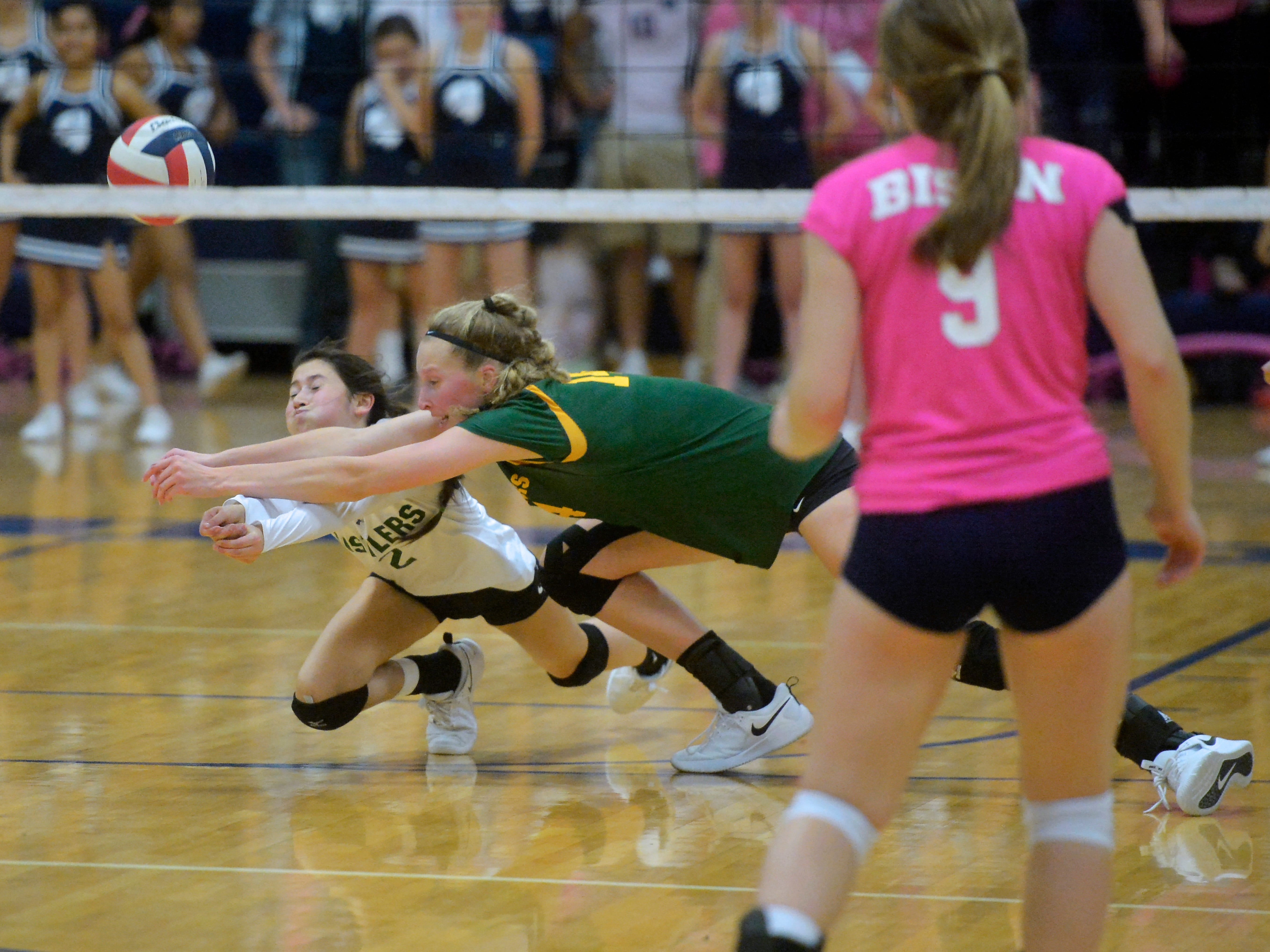 CMR's Lauren Lindseth, 2, and Allie Olsen dive for the ball during crosstown volleyball match in the Swarthout Fieldhouse, Tuesday.