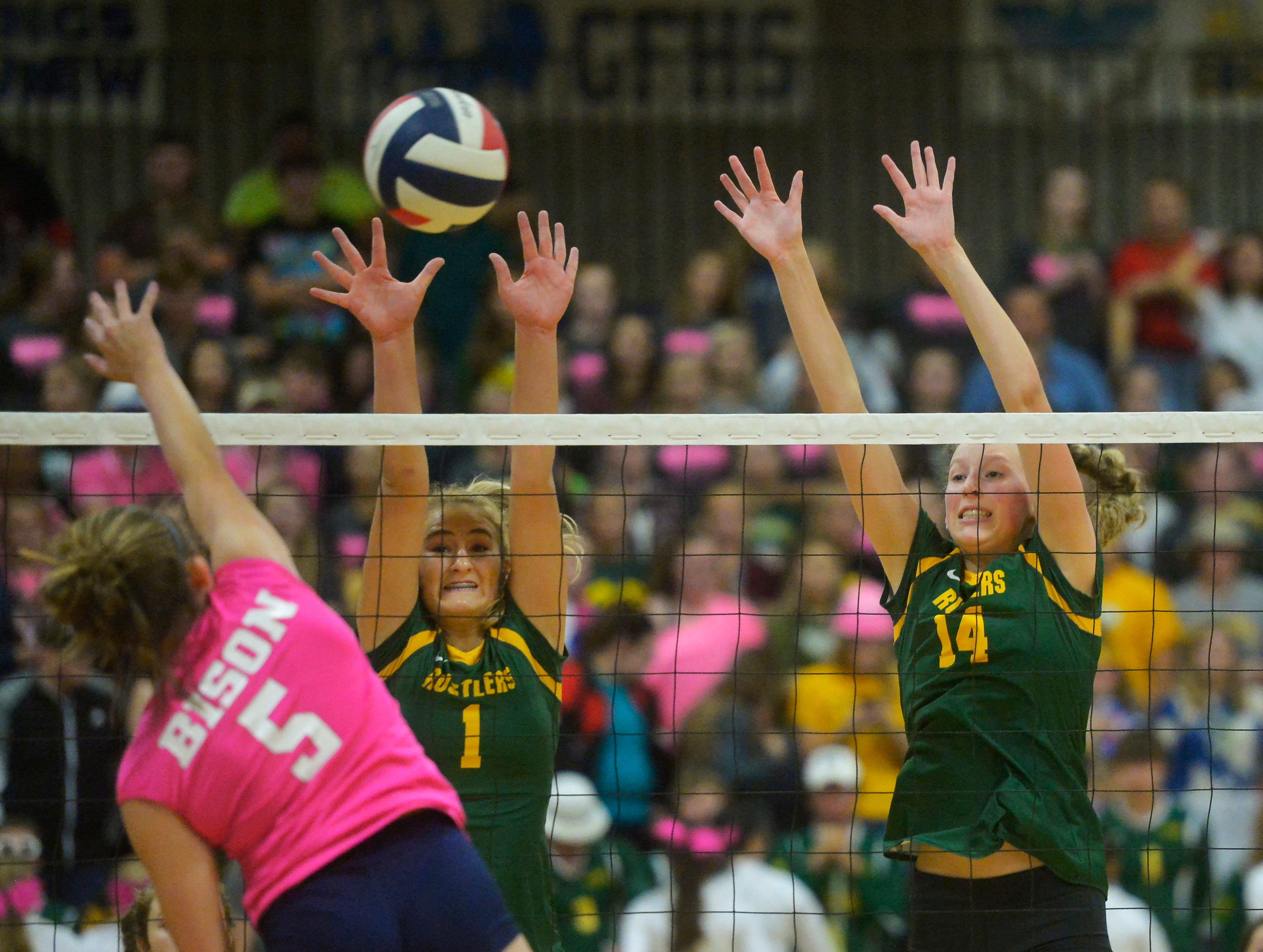 CMR's  Maddie Mohler and Allie Olsen attempt to block a spike by Great Falls High's Kaitlyn Gilbert during the crosstown volleyball match in the Swarthout Fieldhouse, Tuesday.