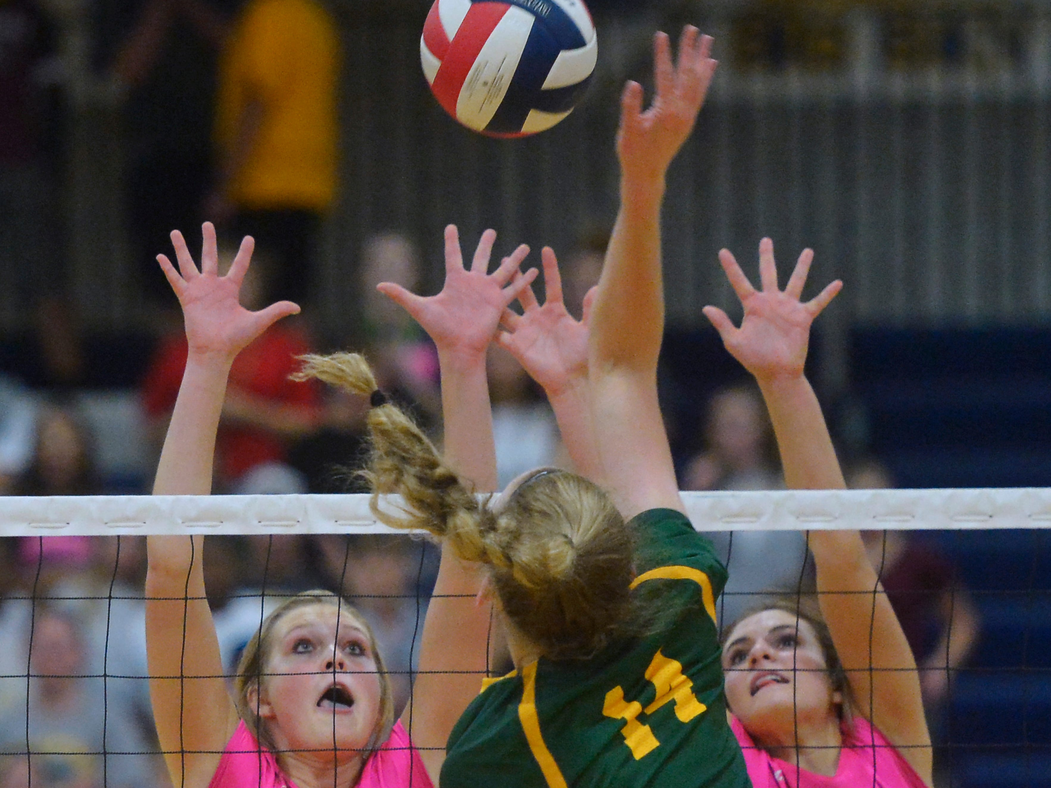 Great Falls High's Abbie Groskreutz, 4, and Hadlee Bleskin, 10, defend the net as CMR's Allie Olsen spikes during the crosstown volleyball match in the Swarthout Fieldhouse, Tuesday.