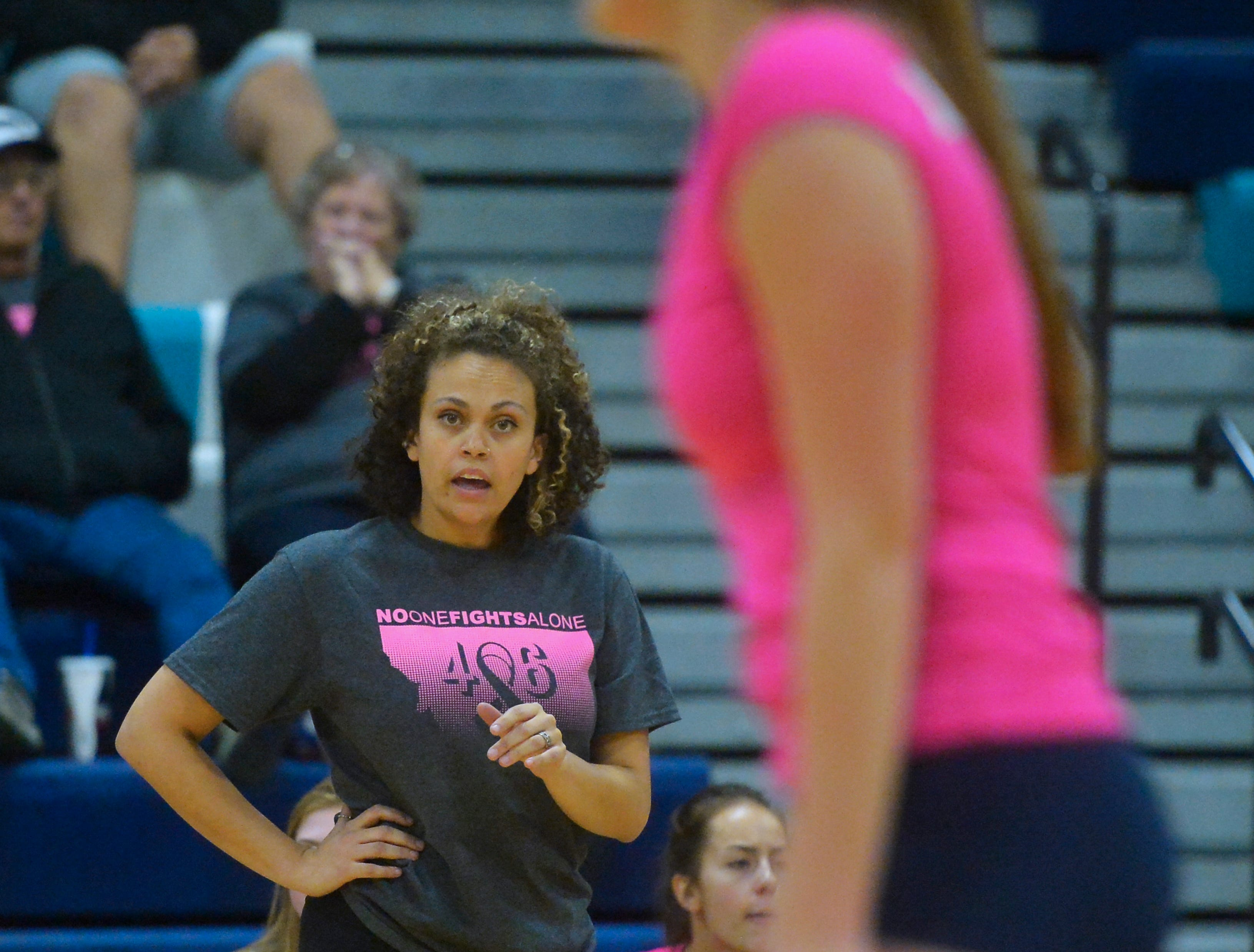 Alissa Blevins talks to her players from the bench during the crosstown volleyball match in the Swarthout Fieldhouse, Tuesday.