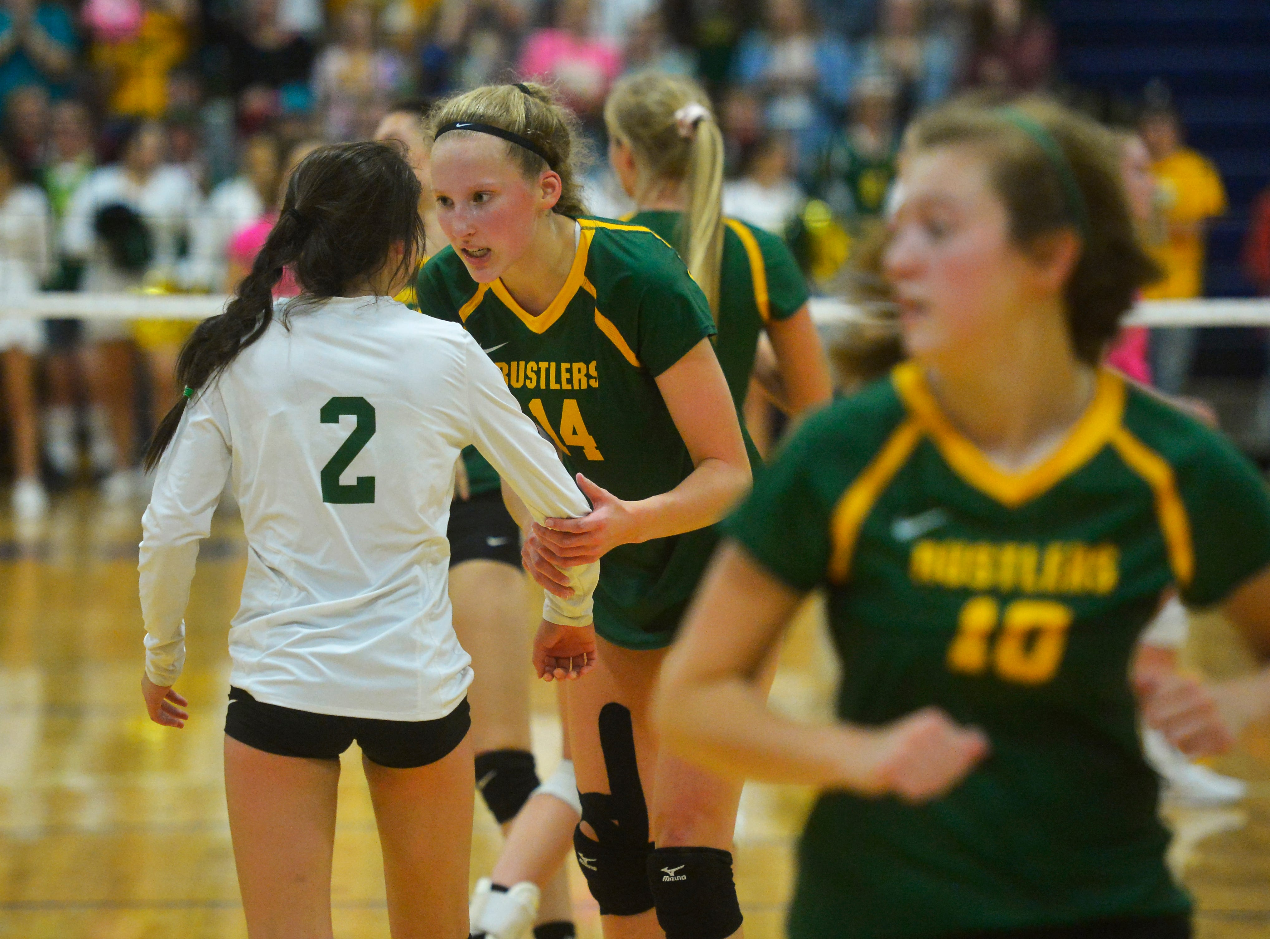CMR's Allie Olsen relays a message to Lauren Lindseth late in the fifth game of the crosstown volleyball match in the Swarthout Fieldhouse, Tuesday.