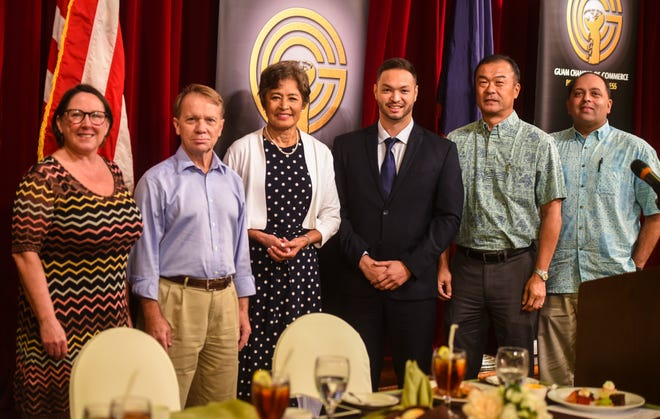 Congressional candidates, center, Doris Flores Brooks and Sen. Michael San Nicolas, gather with  Guam Chamber of Commerce members, from left, Kim Young, Joe Arnett, Mark Tokito and Bobby Shringi, after speaking at the Chamber's membership meeting at the Guam Hilton Resort & Spa in Tumon on Wednesday, Sept. 26, 2018.