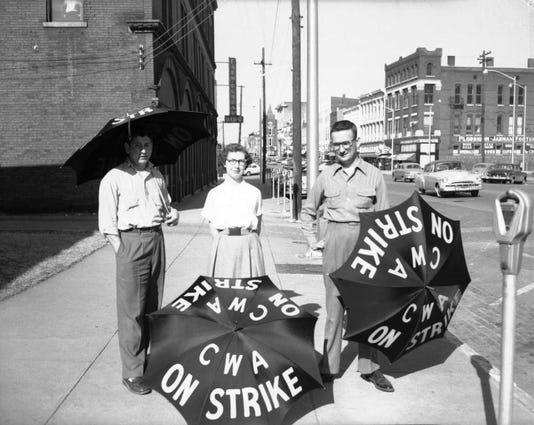 Two men and a woman hold umbrellas in 1955