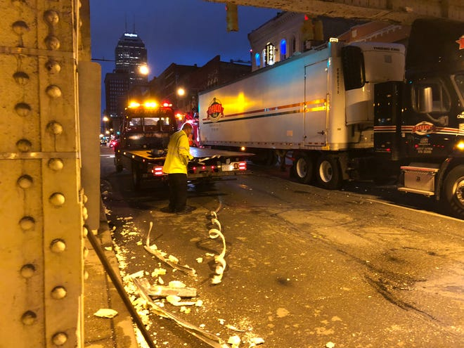 Crew clean up debris left behind after a semi heading south on Meridian Street got struck after hitting the Louisiana Street bridge just before rush hour.