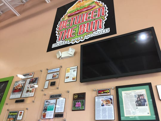 Awards and accolades line wall at the new Between the Bun location, 2222 W. Southport Road, at Ind. 37.