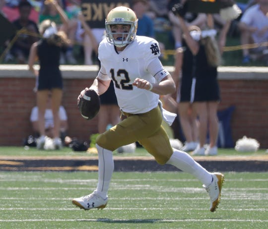 Notre Dame's Ian Book rolls out while looking to pass during his team's game against Wake Forest.