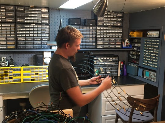 Bobby Getchell prepares to hang a decorative piece as he gets ready to move his vintage stereo sales and repair shop to a new location in Brownburg. Getchell Amplifiers, a vintage stereo and musical equipment, opened in 2014.