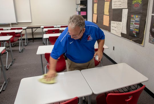 Davey Calvert, custodian at Western Boone High School, works on cleaning off classroom tables. He and his wife owned a restaurant in Jameston, but lost it when the recession hit in 2008.
