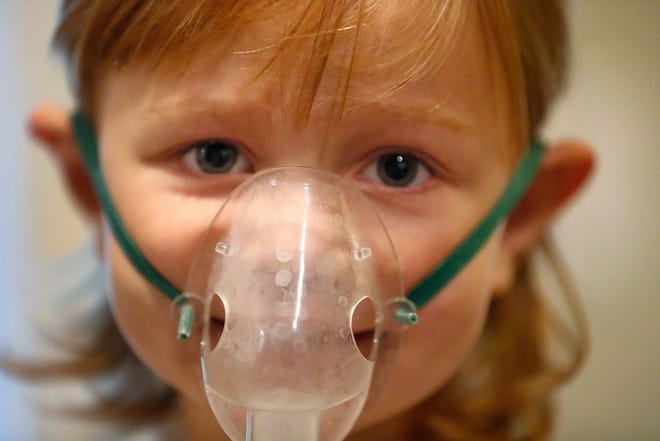 Veda Brand wears a mask to help treat her asthma.