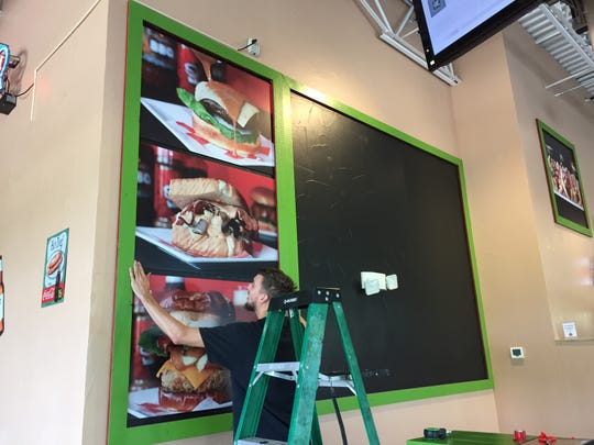 A worker hands up photos of Between the Bun burgers at the restaurant's new location,  2222 W. Southport Road, at Ind. 37, Indianapolis.