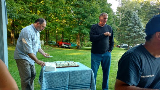 Wayne Myers, right, was recently awarded a Certificate of Appreciation from the West Danby Community Association. The group's Peter Fraissinet cuts the cake.
