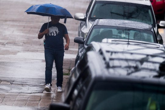 A pedestrian walks through Fort Sanders during an afternoon rain shower in Knoxville on Wednesday.