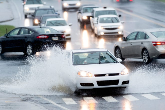 A vehicle drives through a large puddle of standing water in the Western and University Ave. intersection during an afternoon rain shower in Knoxville, Tennessee on Wednesday, September 26, 2018. A flood watch for the area was issued around 1pm until 7pm.