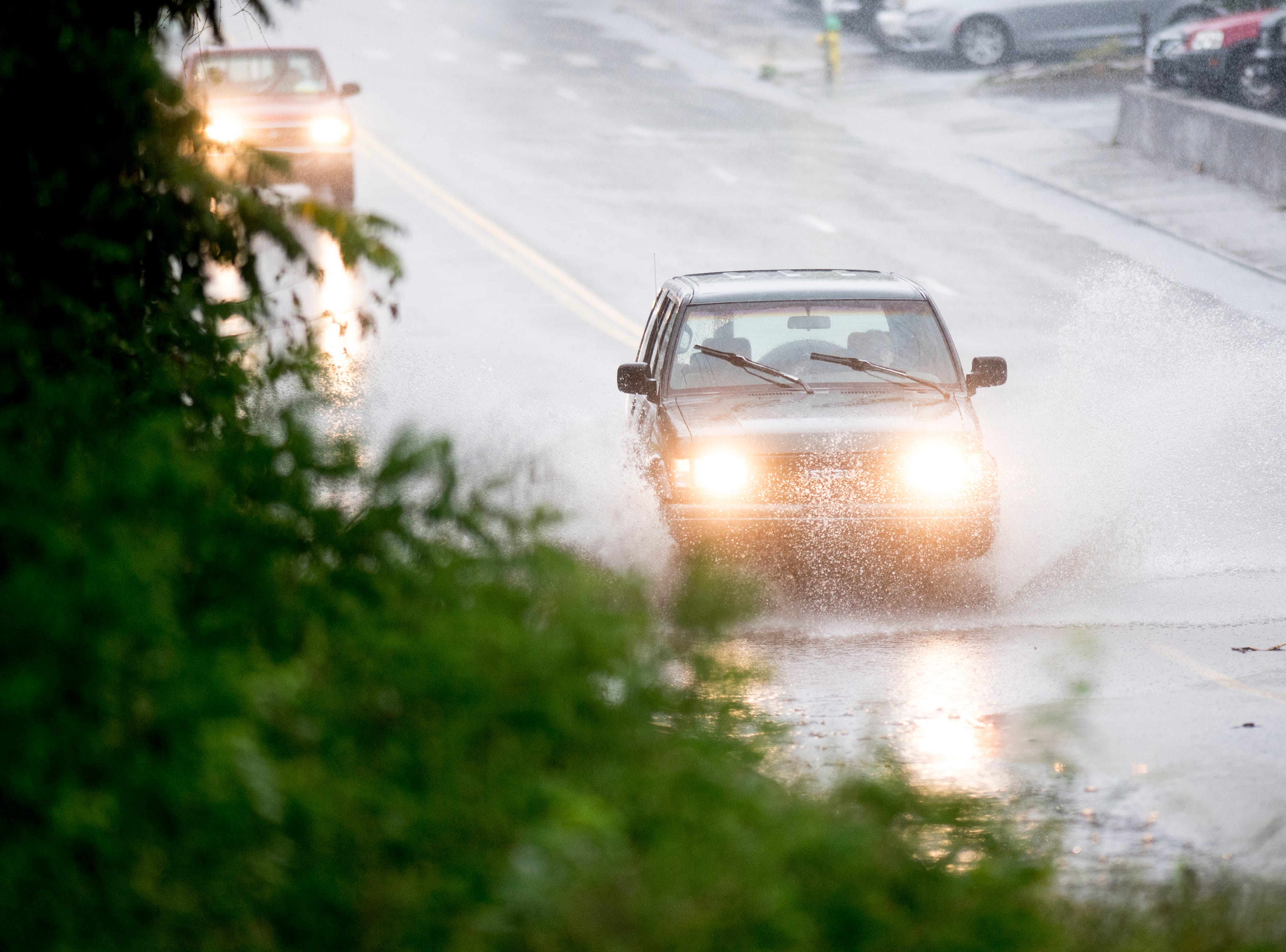 A car drives through a large puddle of standing water on Central Avenue during an afternoon rain shower in Knoxville, Tennessee on Wednesday, September 26, 2018. A flood watch for the area was issued around 1pm until 7pm.