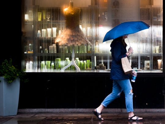A pedestrian walks down Gay Street in the rain on Wednesday, September 26, 2018.