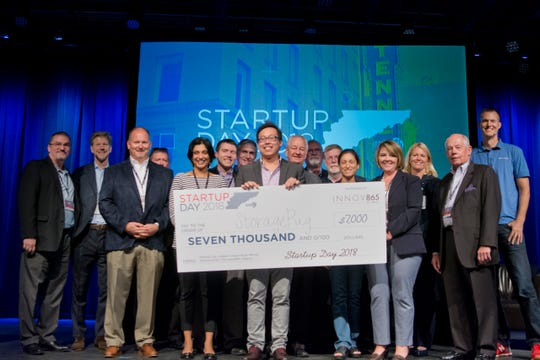 Tommy Nguyen, co-founder and CEO of StoragePug storage facility software company, is presented a $7,000 check at Innov865's Startup Day pitch competition for winning the Judges Choice award. Nguyen also won the $3,000 crowd favorite prize.