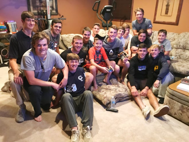 Members of the Central Catholic football team pay a visit to Patrick Dimmitt, a 9-year-old who will have open heart surgery on Thursday.