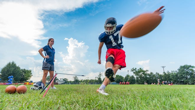 Lafayette Christian senior kicker Colin LaHaye boots a ball during practice as his mother, Knights specialists coach Spring Woodson, looks on.
