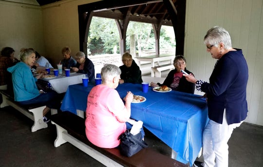 Jackie Shepard, right, reads a text message from Susan Clark's daughter Anegla Clark Tuesday, Sept. 11, 2018, at Rising Park in Lancaster. The group of Susan's friends and former coworkers meet monthly. Susan, who died from breast cancer in 2016, asked her friends to try to meet every month so they could stay in touch with each other.