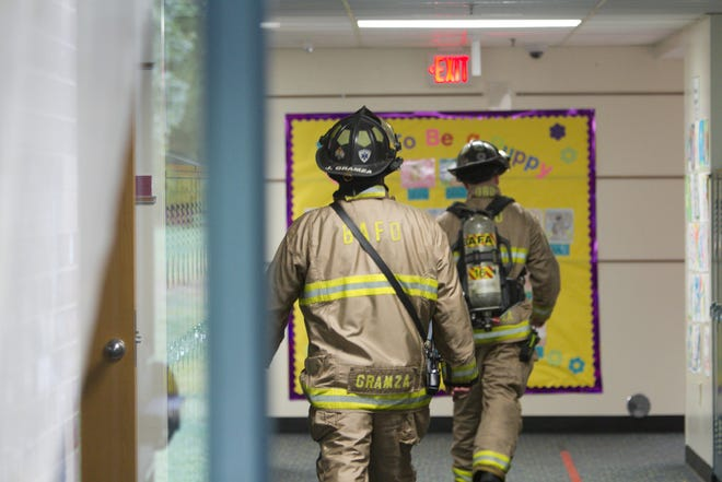 Brighton Area firefighters walk the hallways of Hilton Elementary in Brighton Township Wednesday, Sept. 26, 2018 investigating a report of smoke in the building.