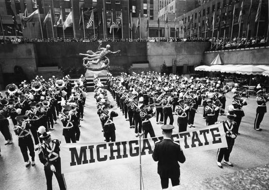 The Michigan State University Marching Band entertains a capacity audience around the Lower Plaza at Rockefeller Center at 5 p.m. on May 18, 1964. During the hour-long program the 140-piece band, under the direction of Leonard Falcone, drew rounds of applause with stirring marches, college songs, and popular numbers. Earlier in the day the band participated in Michigan Day ceremonies at the New York World's Fair.