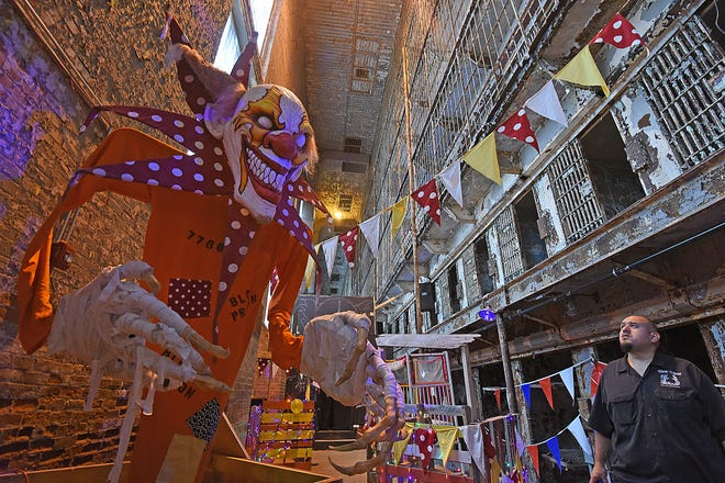 """Vic Amesquita of Undead Studios LLC looks at the 10 foot clown that will scare visitors at the """"Escape from Blood Prison"""" this fall."""