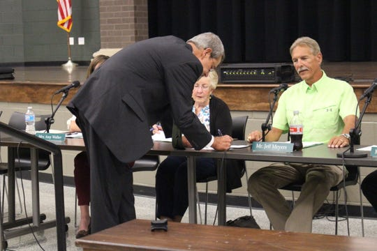 Acting Madison superintendent Lee Kaple, left, signs his contract during a Madison school board meeting Wednesday, Sept. 26, 2018, as board member Jane McGinty and board president Jeff Meyers look on. The board approved a contract to hire Kaple as the district's acting superintendent after relieving superintendent Shelley Hilderbrand of all duties with pay as part of an investigation of allegations she violated board policy.