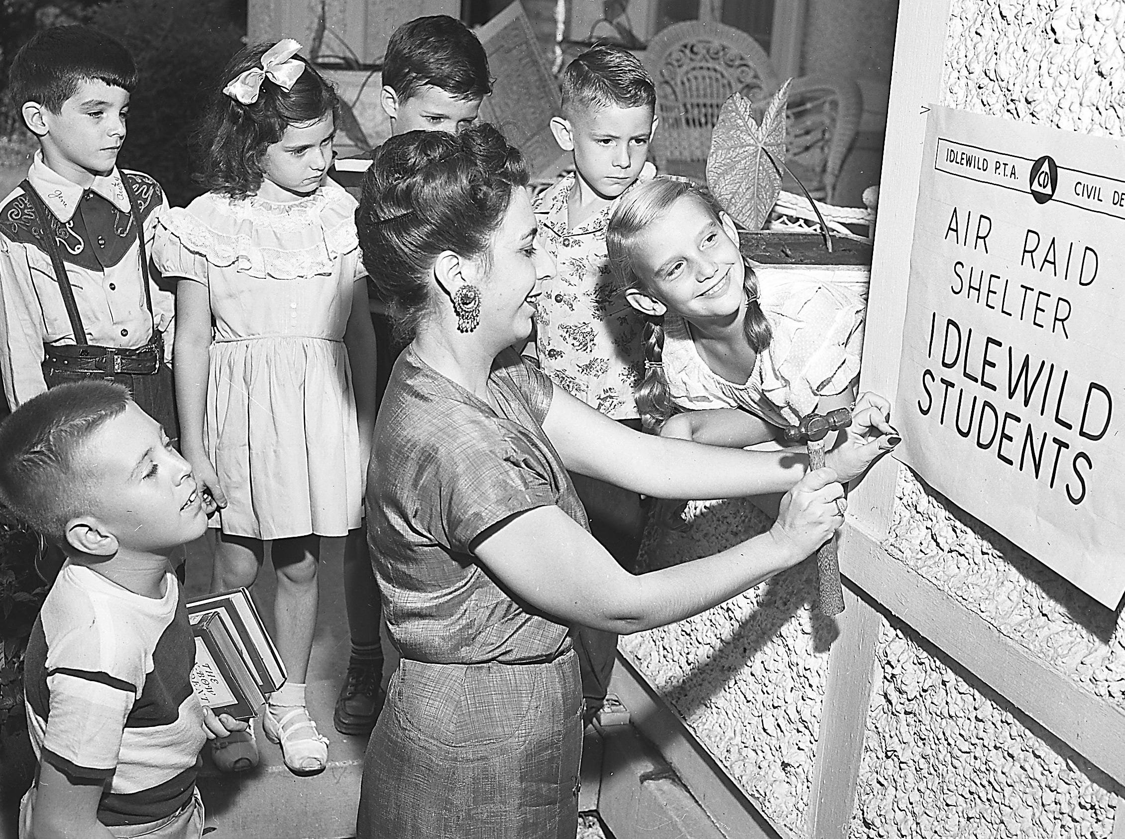 Mrs. Frank Murtaugh of 1845 Cowden, Idlewild P.T.A. member, tacks up a sign designating her home as an air raid shelter for Idlewild school children in case of atomic attack.  Watching the operation on 28 Sep 1951 are (Clockwise from Front Left)  Frank Murtaugh, 9, of 1845 Cowden; Randy Webb, 6, of 1867 Cowden; Patricia Ann Boro, 5, of 1854 Cowden; Jimmy McDonald, 6, of 1881 Cowden; Robert Lee Coker, 6, of 1877 Cowden and Judy Garrecht, 9, of 1834 Cowden.