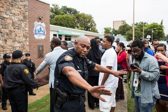 September 26 2018 - A Memphis police officer gets people to move away from the entrance to the Memphis Police Association building after protesters marched to there to demand answers about the shooting of Martavious Banks were released.