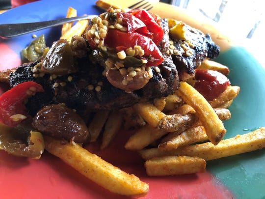 """Steak A La Mama"" ($19.99), a 12 oz. charbroiled sirloin topped with roasted garlic, cherry peppers and ""a la mama"" sauce and was served on top of French fries at the Crazy Flamingo, Marco Island."