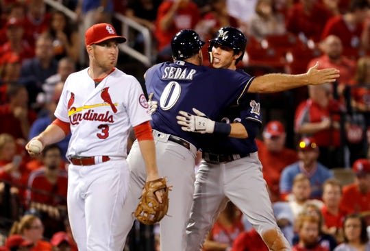 Milwaukee Brewers' Christian Yelich, right, gets a hug from third base coach Ed Sedar (0) after hitting a three-run triple as St. Louis Cardinals third baseman Jedd Gyorko (3) walks past during the fourth inning of a baseball game Tuesday, Sept. 25, 2018, in St. Louis.