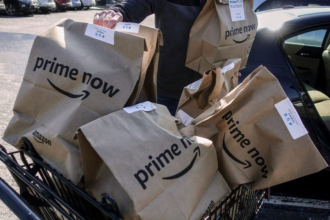 Amazon Prime Now bags of groceries are loaded for delivery outside a Whole Foods store.  Amazon and Whole Foods are expanding their grocery delivery service for Amazon Prime members in  Milwaukee and Madison.