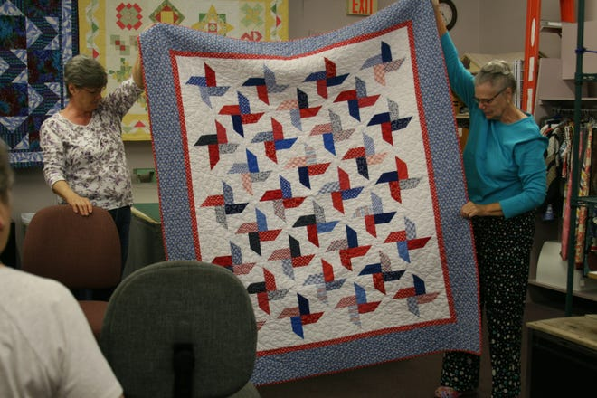 "Carol Whitehead (left) and Sharry Neumann, members of the Mountain Home Quilts of Valor group, display one of their creations during their September meeting. The women meet the fourth Wednesday of the month at 10 a.m. at the Remember Me Quilt Shop on Main Street to create quilts for area service members and veterans who have been ""touched by war."""