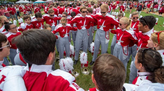The mellophone section circles together to perform their Saturday ritual chant before marching into the stadium.