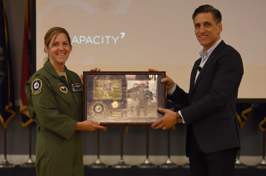 Col. Samantha Weeks, 14th Flying Training Wing commander, hands a gift to Andy Christiansen, motivational speaker, Sept. 14, 2018, on Columbus Air Force Base, Mississippi. Christiansen spoke to hundreds of Airmen here during lectures and small group discussions Sept. 12-14 to give new perspectives on leadership and mentorship.