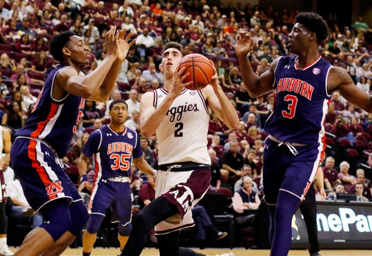 Texas A&M forward Eric Vila (2) goes to the basket against Auburn center Austin Wiley (50) and forward Danjel Purifoy (3), on Feb. 18, 2017, in College Station, Texas.