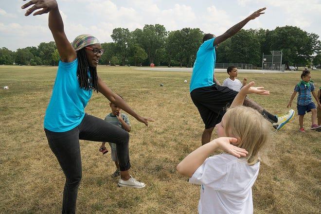 Tatiana Hull and Juwan Perkins lead kids in imitating the movements of different animals.