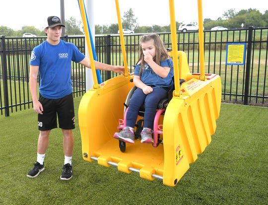 Griffin McAuley pushes Addie Luna during the grand opening of Mary's Magical Place, an all-inclusive playground in Hendersonville on Tuesday, Sept,.25, 2018.  Mary's Magical Place is named for Griffin's sister, Mary McAuley, a Hendersonville teen who died from complications of cerebral palsy in 2015.