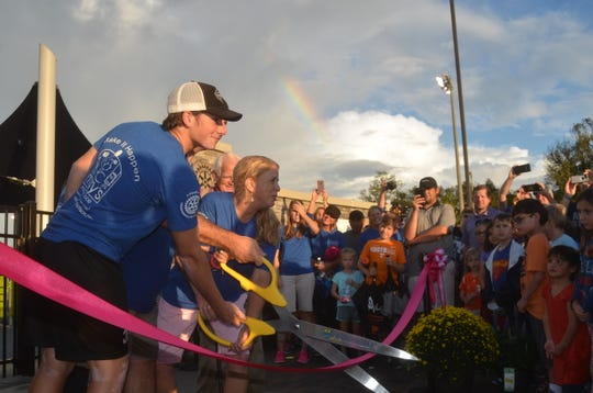 A rainbow peeks through as the McAuley family cuts the ribbon at Mary's Magical Place, an all-inclusive playground in Hendersonville.